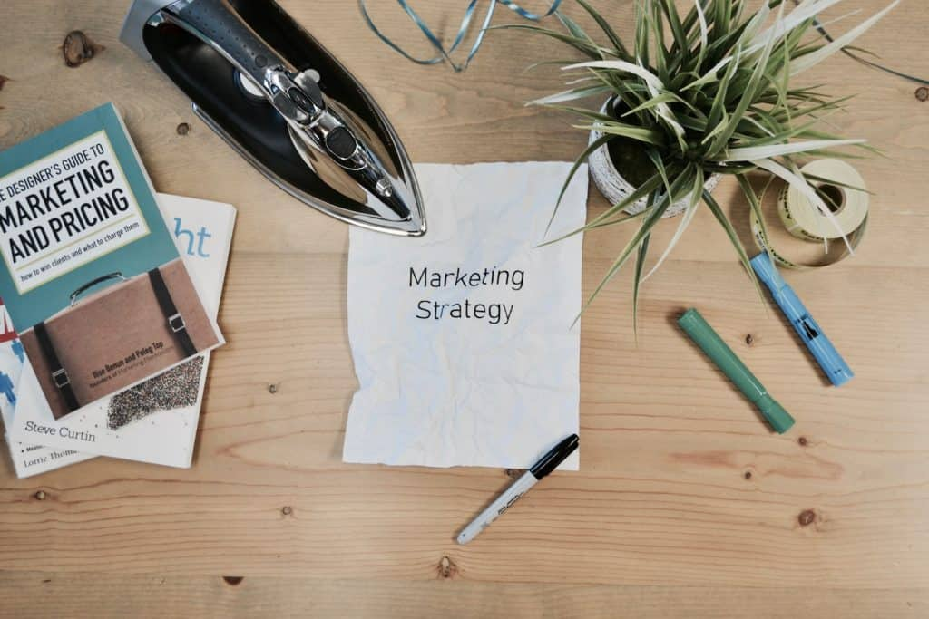crumpled paper that says Marketing Strategy next to an iron